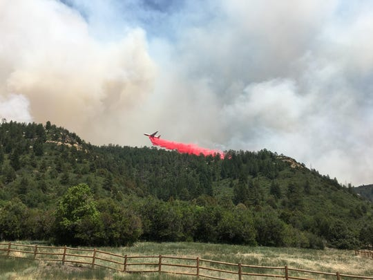 A plane drops retardant on the East Canyon Fire, Monday, June 15, 2020, in Colorado.