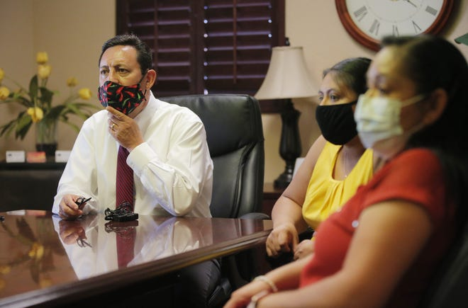 Lawyer Robert J. Campos talks about his client, Kevin Andrade-Andrade, with his girlfriend Jennifer Medina (center) and mother Natalia Andrade Rosas at his office in Phoenix June 15, 2020. The Maricopa County inmate has tested positive for COVID-19.