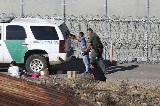 En esta fotografía de archivo del 15 de diciembre de 2018, tomada desde la ciudad mexicana de Tijuana, hondureños que solicitan asilo son detenidos por agentes de la Patrulla Fronteriza.