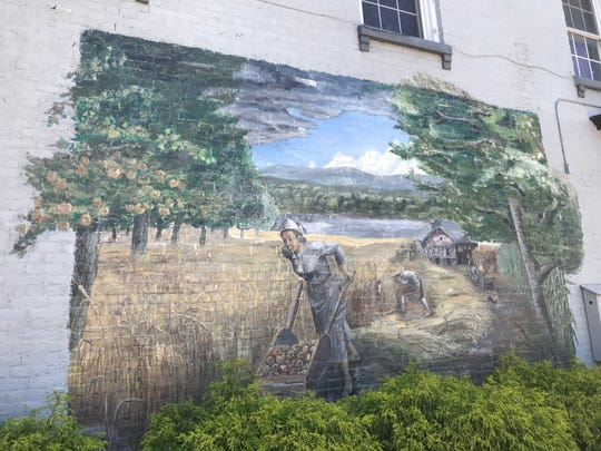 A mural designed to celebrate local history and spur tourism when it was painted in 1996 is now stirring controversy over race.