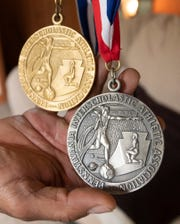Simmie Strasbaugh holds gold and silver track medals from the early 1990s.