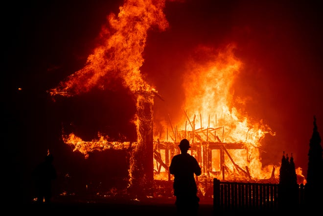 FILE - In this Nov. 8, 2018 file photo, a home burns as a wildfire called the Camp Fire rages through Paradise, Calif. Pacific Gas & Electric officials are to be expected to appear in court Tuesday, June 16, 2020, to plead guilty for the deadly wildfire that nearly wiped out the Northern California town of Paradise in 2018. (AP Photo/Noah Berger, File)