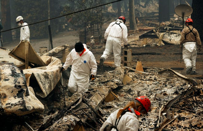 FILE - In this Nov. 13, 2018, file photo, search and rescue workers search for human remains at a trailer park burned out from the Camp Fire in Paradise, Calif. Pacific Gas & Electric officials are to be expected to appear in court Tuesday, June 16, 2020, to plead guilty for the deadly wildfire that nearly wiped out the Northern California town of Paradise in 2018. (AP Photo/John Locher, File)