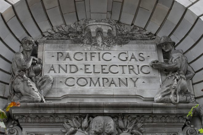 FILE - In this April 16, 2020, file photo, a Pacific Gas & Electric sign is displayed on the exterior of a PG&E building in San Francisco. Pacific Gas & Electric officials are to be expected to appear in court Tuesday, June 16, 2020, to plead guilty for the deadly wildfire that nearly wiped out the Northern California town of Paradise in 2018. (AP Photo/Jeff Chiu, File)