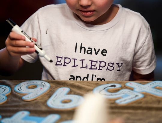 Hayden Cota traces numbers at his kitchen table on Tuesday, March 17, 2020 in Sioux Falls, S.D. Cota has epilepsy and his parents, Karen and Tom, hope to bring awareness.