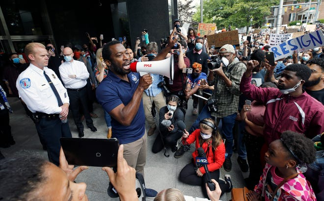 Richmond Police Chief William Smith, left, listens as Mayor Levar Stoney, right, addresses a crowd outside Richmond City Hall in Richmond on June 2.