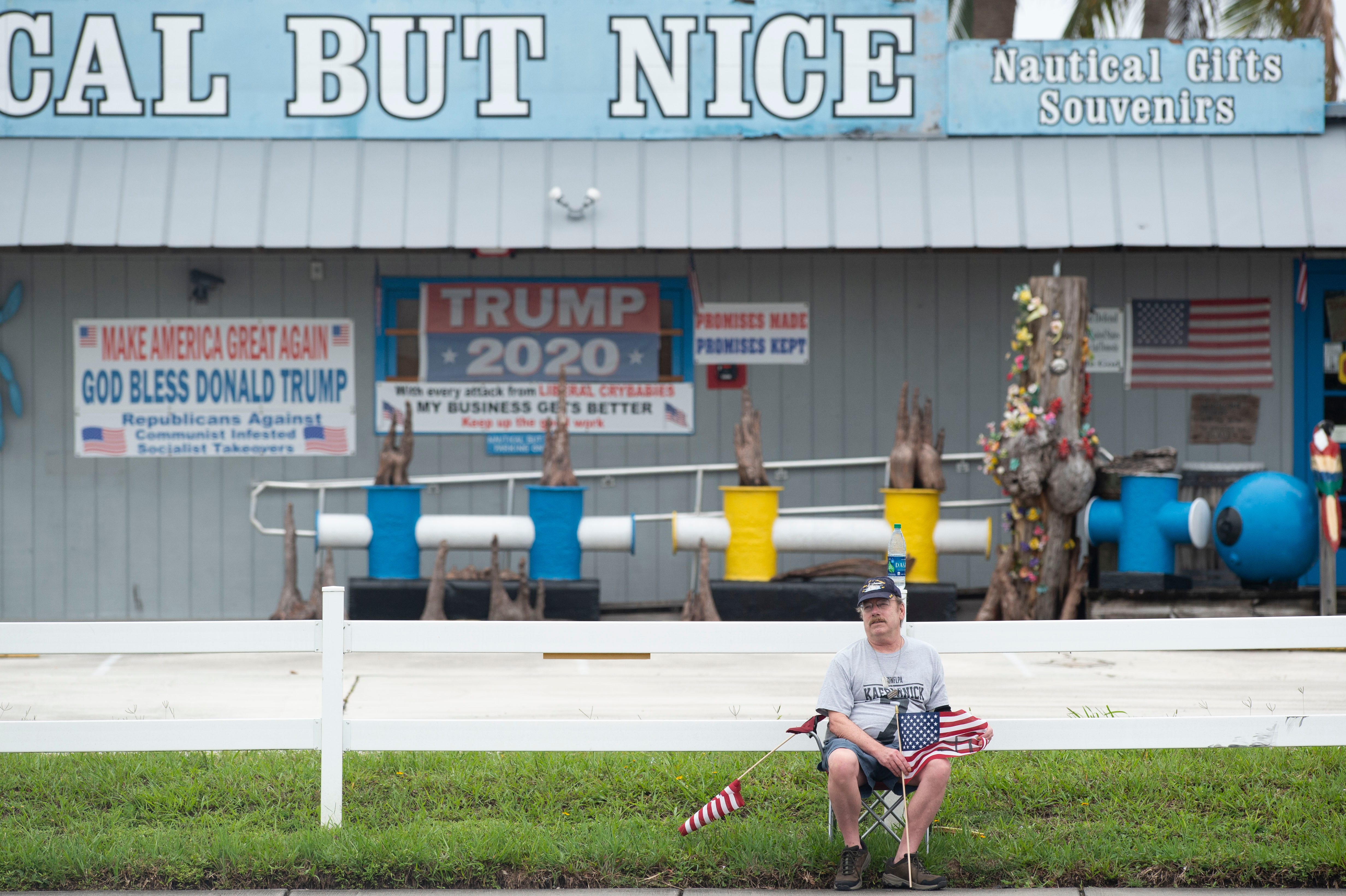 """Nathan Dodge, of Stuart, stays separate from a group of more than 250 people who gathered for a Black Lives Matter protest along U.S. 1 at the intersection of Southeast Luckhardt Street on Saturday, June 6, 2020, in Stuart. Within a couple of hours, people filled the east and west sides of the sidewalk in front of several businesses, including Nautical But Nice and Chick-fil-A. """"Liberty and justice for all doesn't mean anything anymore, that's why America sucks,"""" Dodge said of why he was protesting."""