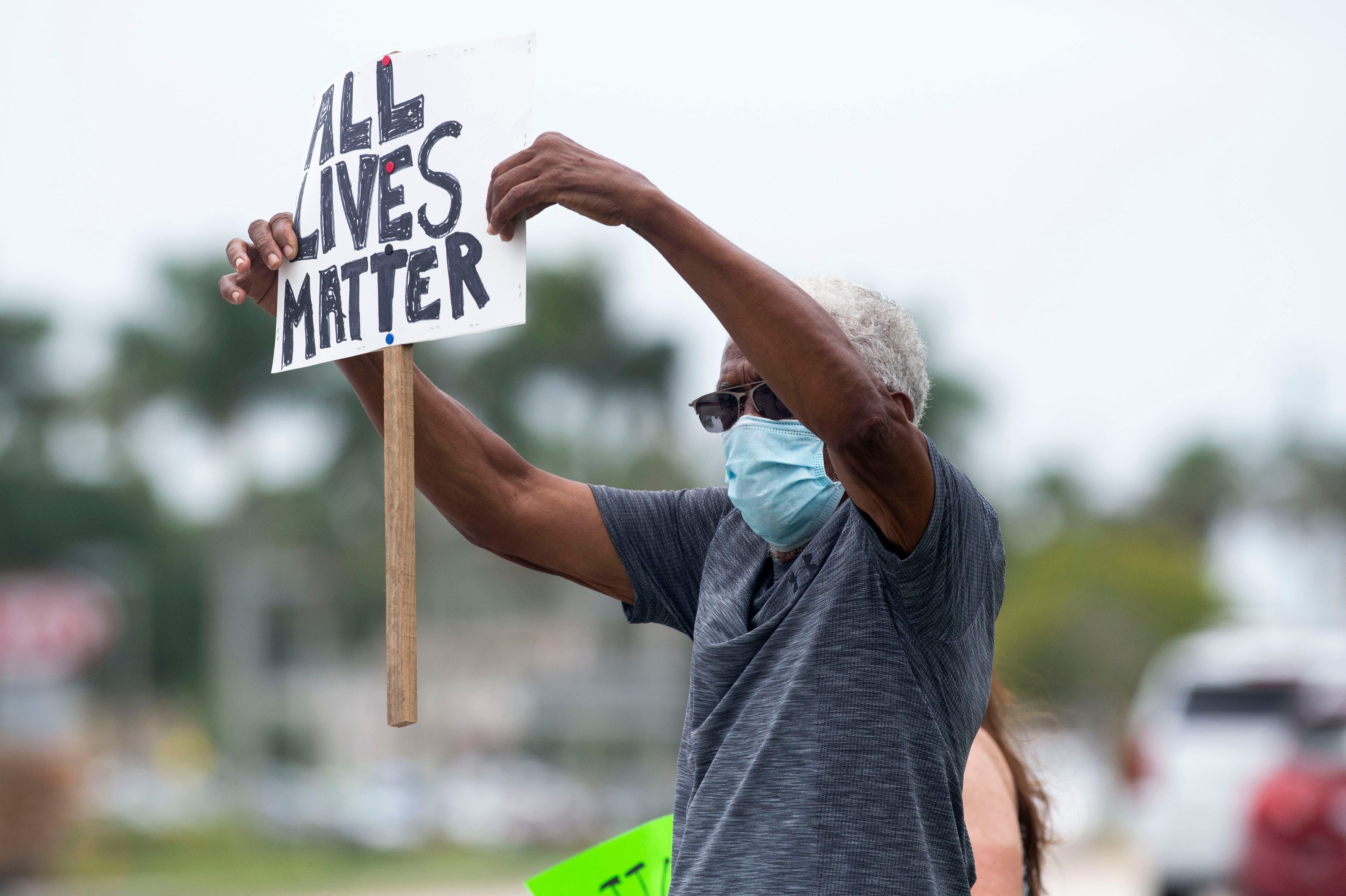 """Germaine Patterson, of Martin County, holds up a sign that says """"all lives matter"""" on one side and """"also your vote matters"""" on the other during a Black Lives Matter protest along U.S. 1 at the intersection of Southeast Luckhardt Street on Saturday, June 6, 2020, in Stuart. """"I was out last week and I also came out this week because my grandson was organizing,"""" Patterson said. His grandson, Robert Parent, organized the protest that drew more than 250 people."""