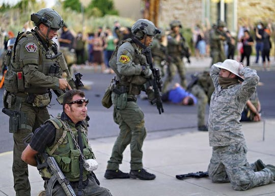 Albuquerque police detain members of the New Mexico Civil Guard, an armed civilian group, following the shooting of a man during a protest over a statue of Spanish conquerer Juan de Oñate on Monday, June 15, 2020.