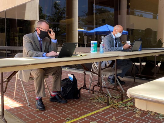 Public defenders Russell Baker, left, and Michael Albers helped people with their criminal cases at a table outside Ventura County Superior Court on Monday, June 15, 2020, when the court reopened with modified operations due to the coronavirus.