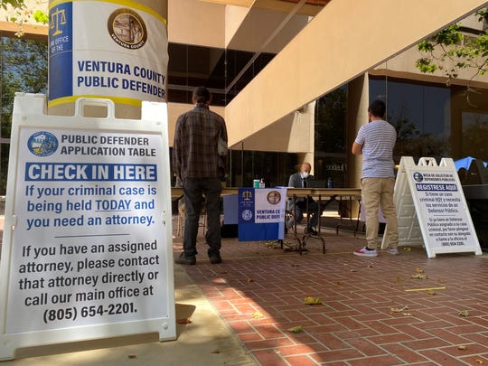 Public Defender Michael Albers, seated, looks up case information at a table outside Ventura County Superior Court on Monday, June 15, when the facility reopened with modified operations due to the coronavirus.