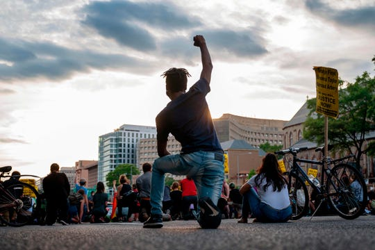 A protester kneels and holds up a fist as he and others demonstrate the death of George Floyd by closing down and blocking traffic on I-395 in Washington, DC on June 15.