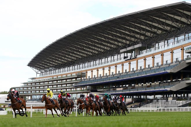 Jockeys and their horses pass the empty stands during a race on Day 1 of the Royal Ascot horse racing meet in Ascot, west of London, on June 16, 2020. The event is taking place behind closed doors due to the ongoing novel coronavirus pandemic.