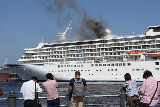 Black smoke rises from the Japanese cruise ship Asuka II docked in Yokohama Port, near Tokyo, Tuesday, June 16, 2020. The local branch of Japan Coast Guard said smoke started on the top floor of the one of Japan's largest cruise ship where dozens of firefighters were battling to extinguish it. The coast guard said there were no reports of injuries.