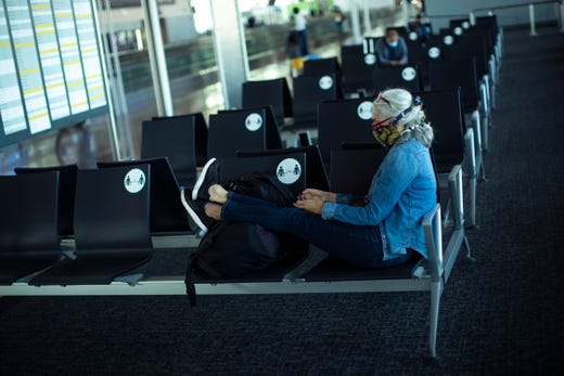 A passenger, wearing a face mask to protect against the spread of coronavirus, sits before boarding her flight at the Zaventem international airport during the partial lifting of coronavirus COVID-19 lockdown regulations in Brussels, Monday, June 15, 2020. Borders opened up across Europe on Monday after three months of coronavirus closures that began chaotically in March.