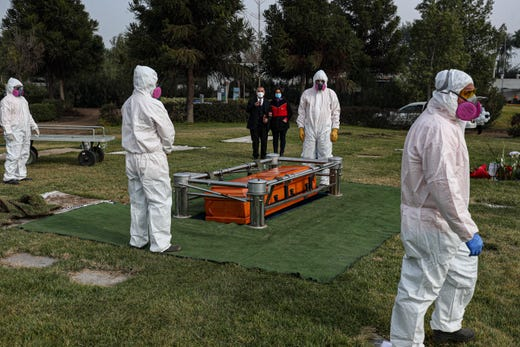 Cemetery workers wearing protective gear against the new coronavirus, walk after carrying the coffin of 72-year-old Monica Lagos to her grave at the Manantial cemetery in Santiago, Chile, Monday, June 15, 2020. According to her grandaughter Ninoska Vasquez, who works as an assistant at a health center, Lagos died from complications related to COVID-19.