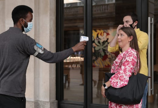 A woman reacts as she gets her temperature checked outside the Apple store in Covent Garden on June 15, 2020 in London, United Kingdom. The British government have relaxed coronavirus lockdown laws significantly from Monday June 15, allowing zoos, safari parks and non-essential shops to open to visitors. Places of worship will allow individual prayers and protective face-masks become mandatory on London Transport.