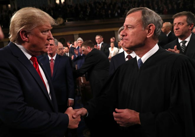 President Donald Trump greets Supreme Court Chief Justice John Roberts as he arrives to deliver his State of the Union address on February 4, 2020.