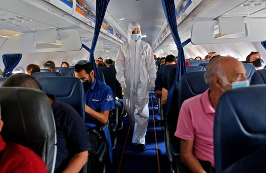 An Israir Airlines flight attendant wearing full PPE (personal protective equipment) prepares for take off from the Ben Gurion International Airport near the central Israeli city of Tel Aviv to southern Israeli Red Sea resort city of Eilat amid the COVID-19 pandemic, on June 16, 2020.