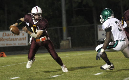 Grant's quarterback Dillon Barrett (14) evades Peabody's Gus Snowden on a keeper gains over twenty yards and   a first down during a 2010 game. Barrett was recently named the new football coach at Grant.