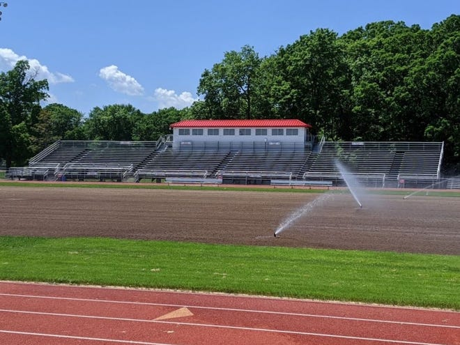 Sprinklers water the newly graded and seeded football field at Neenah High School.