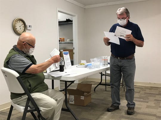 Republican Dyatt Smathers and Democrat chair Jerry Wallin of the Madison County Board of Elections review signatures on absentee mail in ballots during a June 16 meeting.
