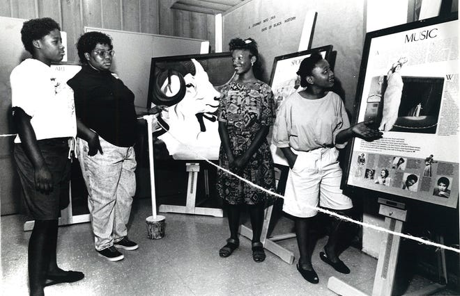 Rosann Perry, 14, (left to right) and Shirley Johnson view the display of Black art at T.C. Ayers Recreation Center on Winnebago Street in Corpus Christi as Faithful Cannon, 14, and Shellan Porter, 14, explain the exhibit during Juneteenth celebrations on June 14, 1991.