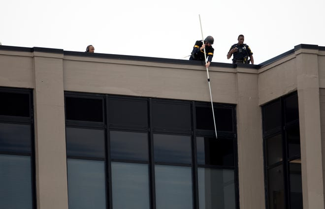 Police use a pole to tap on a fourth floor window of the Lighthouse Sheakley Center for Youth where police say a man has barricaded himself with a weapon and is threatening to harm himself.