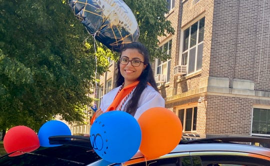 Linden High School Valedictorian Sarah Mostafa at a pre-graduation drive-through event at the school, which celebrated graduates and where staff members volunteered to hand out caps and gowns and other special gifts.