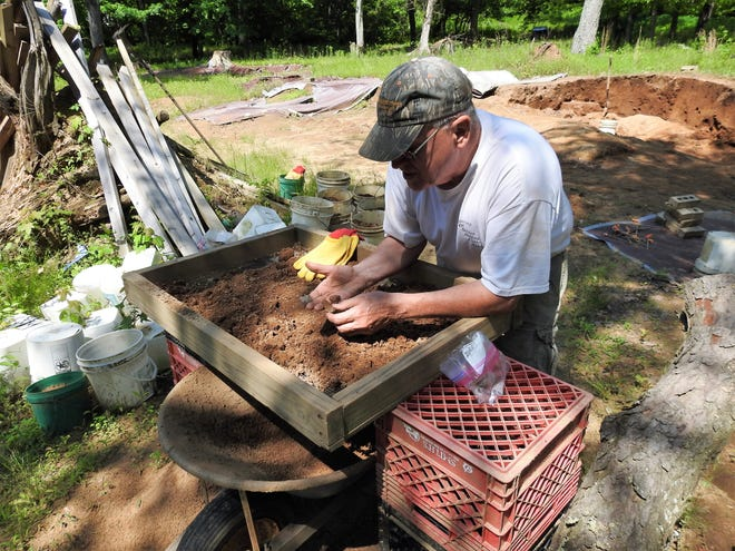 Mark Hersman sifts through dirt looking for artifacts from prehistoric people at a site in eastern Coshocton County. The one-acre site was home to a Native American village that spanned generations. He routinely finds arrowheads, flint and pieces of pottery.