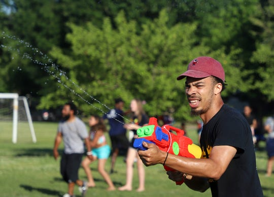 Matthew Bruce participates in a squirt gun fight at a community event hosted by Laced Up Family at Evelyn K. Davis Park in Des Moines on June 16.