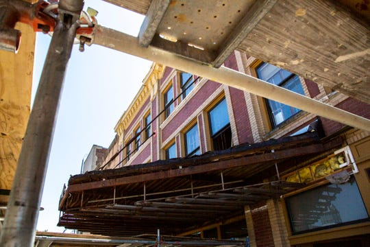 Rusted metal and rotting wood is seen below the face of the marquee at the Englert Theatre as pieces are removed while construction crews work on a renovation project, Tuesday, June 16, 2020, along Washington Street in Iowa City, Iowa.