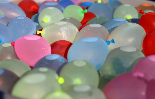 A bucket of water balloons sit at a community event hosted by Laced Up Family at Evelyn K. Davis Park in Des Moines on June 16.