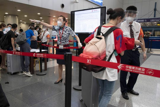 Airline employees redirect a traveller at a checkpoint for passengers from high risk areas to present their COVID-19 test results before checking in for their flight at the Beijing Capital Airport terminal 2 in Beijing on Wednesday.