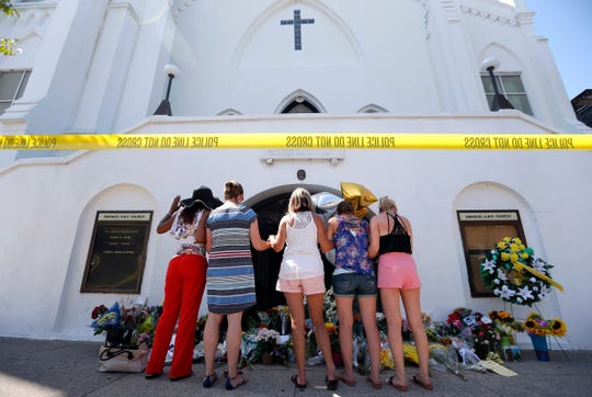 In this June 18, 2015, file photo, a group of women pray at a makeshift memorial on the sidewalk in front of the Emanuel AME Church in Charleston, S.C.