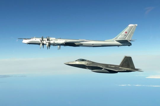 In this image taken Tuesday, June 16, 2020,  and released by the North American Aerospace Defense Command, a Russian Tu-95 bomber, top, is intercepted by a U.S. F-22 Raptor fighter off the coast of Alaska.