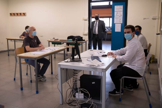 Edoardo D'Alba, 19, wearing a mask to prevent the spread of COVID-19, right, sits at a desk before the examiners at a high school Liceo Morgagni to do his end of year secondary school exams, in Rome, Wednesday.