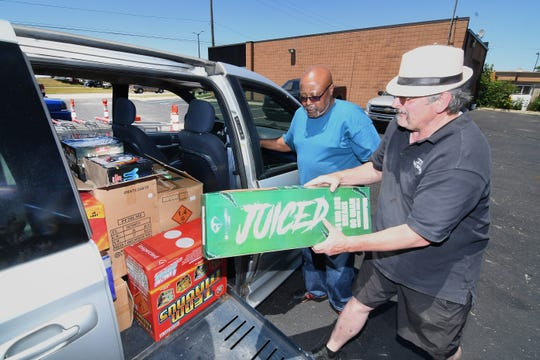 Robert Bahnke, right, regional manager for Pro Fireworks, helps Frank Woodard load up $1,200  worth of fireworks at the Sterling Heights store.