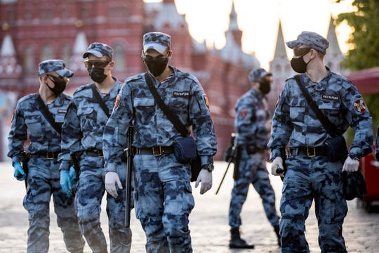 Russian Rosguardia (National Guard) soldiers wearing face masks and gloves to protect against coronavirus, guard an area on Red Square before a rehearsal of the military parade near Red Square in Moscow, Russia, Sunday, June 14, 2020.