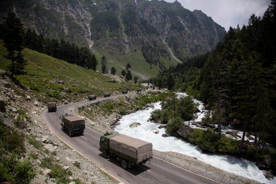An Indian army convoy moves on the Srinagar- Ladakh highway at Gagangeer, north-east of Srinagar, India, Wednesday.
