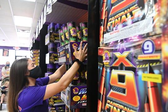 Alaina Macksoud, a cashier at Phantom Fireworks, stocks one of the many prepackaged firework bundles at Phantom Fireworks of Sterling Heights on June 17, 2020.