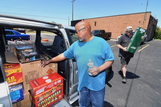 Frank Woodard (left) is assisted by Robert Bahnke, regional manager, Pro Fireworks, fills Woodard's Dodge Caravan with hundreds dollars worth of fireworks from Pro Fireworks in Sterling Heights on June 17, 2020 for the Fourth of July holiday and beyond.
