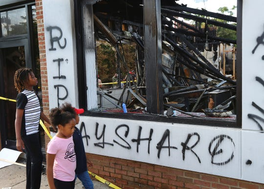 Children take in the burned Wendy's location in Atlanta on Monday, June 15, 2020, outside which Rayshard Brooks, a 27-year-old black man, was fatally shot by a white Atlanta police officer Friday night.