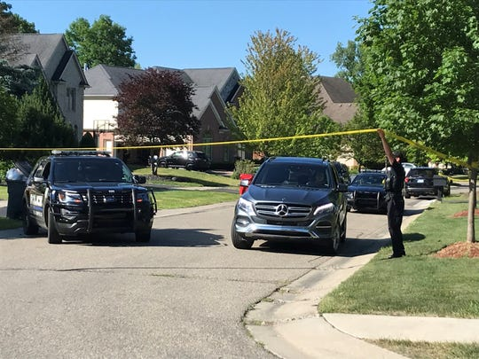 West Bloomfield police move crime scene tape so drivers on Chase Court can pass. A homeowner reported shots fired in the early hours of Wednesday, June 17, 2020. He was wounded and a man was found dead. Another man in a Dodge Charger was arrested; he, too, had a gunshot wound.