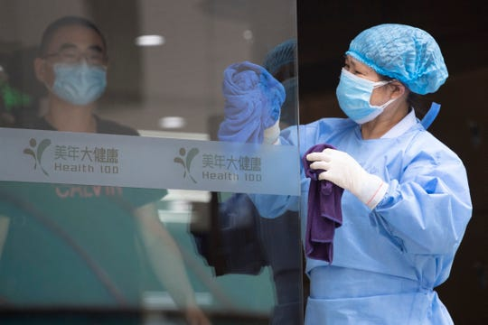 A worker cleans the glass door to a health center for COVID-19 testing in Beijing on Wednesday.