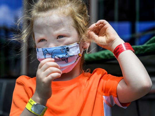 Amilia Templeton, 5, adjusts her face mask before taking a break for lunch with her family during their first trip of the season to Holiday World & Splashin' Safari in Santa Claus, Ind., Wednesday morning, June 17, 2020. This year each guest will be given a wristband featuring a QR code, like the red one pictured on Templeton's wrist, to register for ride times to cut down on lines.
