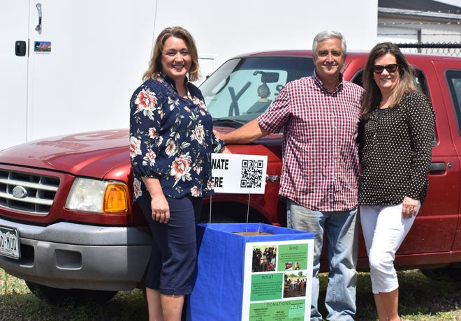 Lara Holt, left, and family friends Scott and Julie Nackos of Windsor stand next to the Ford Ranger pickup that belonged to Kyle Nackos, who was killed in a vehicle crash in this photo taken June 16, 2020. The Nackos are donating their son's pickup to a project headed by Holt that will help a teacher in West Africa.