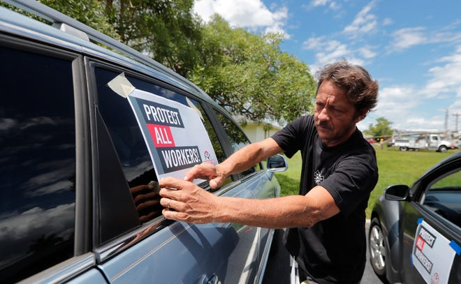 Cape Coral resident Mark Potter adheres a placard onto his car as union workers with the Florida AFL-CIO prepare to parade around the Mid Cape Coral Post Office on Wednesday, raising awareness for the U.S. Postal Service.