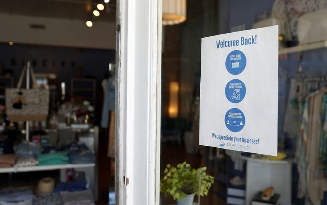 "A ""Welcome back"" sign in the window of Blue Ivy on June 12, 2020, asks customers to wear a mask, use hand sanitzer before entering and social distance while inside the Sturgeon Bay clothing store."