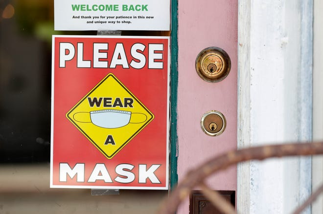 "A sign on a business asks patrons to ""please wear a mask."""